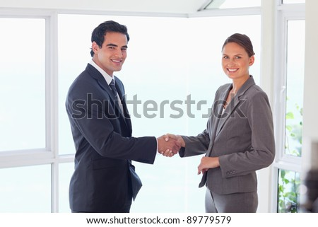 Side view of smiling young trade partner shaking hands - stock photo