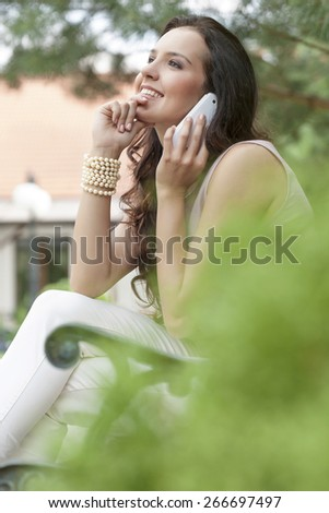 Side view of smiling young woman using mobile phone in park - stock photo