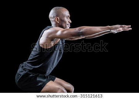 Side view of sportsman squatting against black background - stock photo