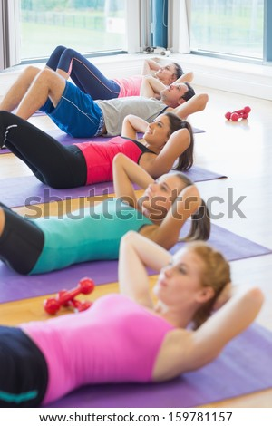 Side view of sporty fitness class doing sit ups on exercise mats - stock photo