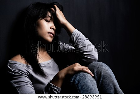 side view of stress woman leaning on dark wall - stock photo