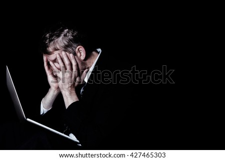 Side view of stressed business man, holding his head, with laptop in front of him.  Dark background with light on subject.   - stock photo
