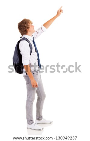 side view of teen boy pointing at empty copyspace - stock photo