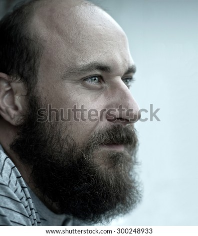 Side view of the bald man with beard seriously looking in the distance. Desaturated image, vintage look  - stock photo
