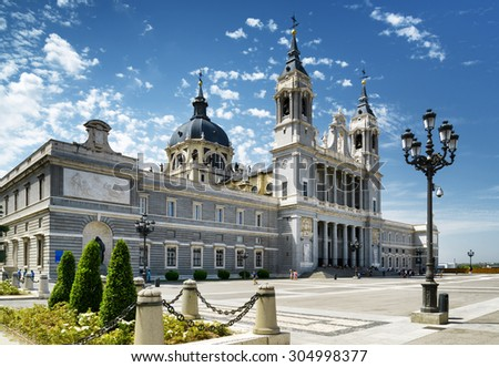 Side view of the Cathedral of Saint Mary the Royal of La Almudena on the blue sky background with white clouds in Madrid, Spain. Madrid is a popular tourist destination of Europe. - stock photo