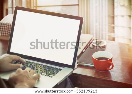 side view of the laptop is on the work table in a conner office with morning light. - stock photo