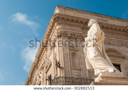 Side view of the statue of St. Peter outside of the Cathedral of Syracuse and the Palazzo Vermexio behind it - stock photo
