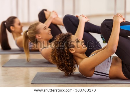 Side view of three attractive sport girls smiling while working out lying on yoga mat in fitness class - stock photo
