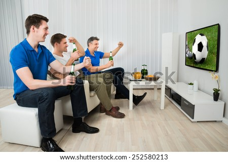 Side View Of Three Men Sitting On Couch Watching Football Match On Television - stock photo