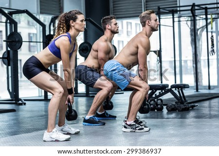 Side view of three muscular athletes squatting with kettlebells - stock photo