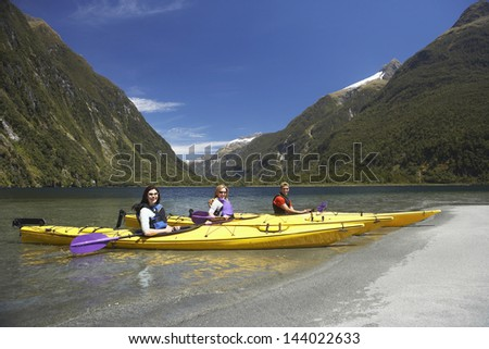 Side view of three young people kayaking in the lake with mountains in background - stock photo