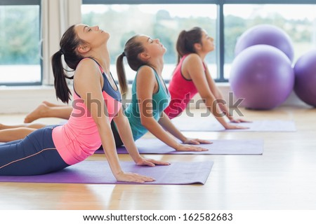 Side view of trainer with class doing the cobra pose in bright fitness studio - stock photo
