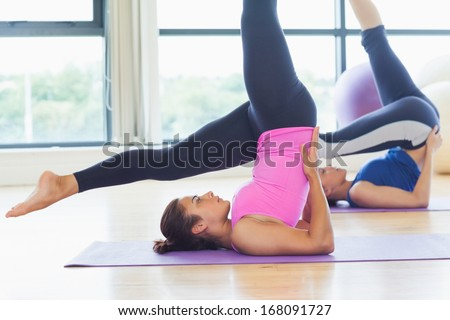 Side view of two fit women doing the shoulder stand posture in fitness studio - stock photo