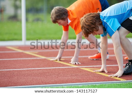 Side view of two young male runners on starting position at racetrack - stock photo