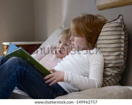 Side view of two young sisters reading book on a bed - stock photo