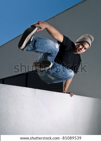 side view of urban parkour free runner jumping over a wall - stock photo