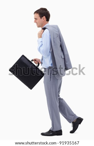 Side view of walking and smiling businessman with suitcase against a white background - stock photo