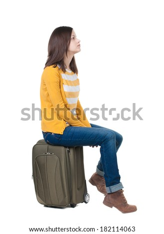 side view of walking  woman  in cardigan sits on a suitcase. beautiful  girl in motion.  backside view of person.  Rear view people collection. Isolated over white background. - stock photo
