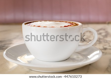 Side view of white ceramic cup of hot cappuccino coffee with holder on the right side. The item is on light yellow marble table top with plate coaster - stock photo