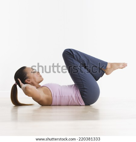 Side view of woman doing crunches - stock photo