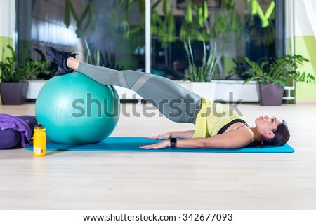 Side view of woman doing half bridge pose in fitness studio practices piltes or yoga warming up exercises for spine, backbend, strengthening back muscles. - stock photo