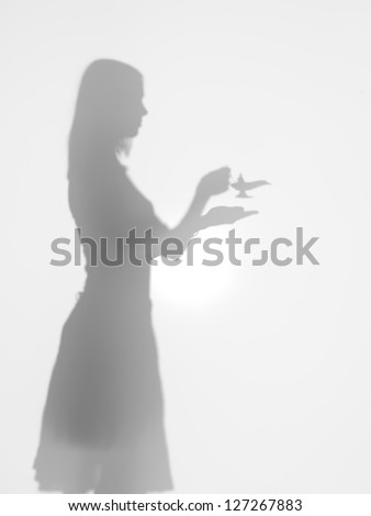 side view of woman holding the lamp of alladin in her hands, behind a diffuse surface - stock photo