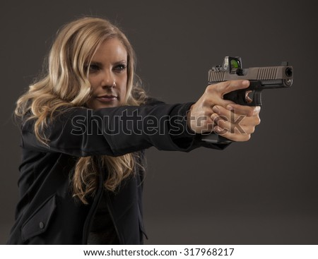 Side view of woman shooter aiming weapon. - stock photo