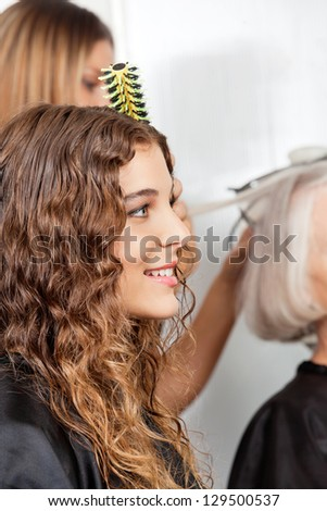 Side view of woman with hairdresser and client in the background at salon - stock photo