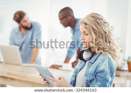 Side view of woman with headphones while using digital tablet in office - stock photo