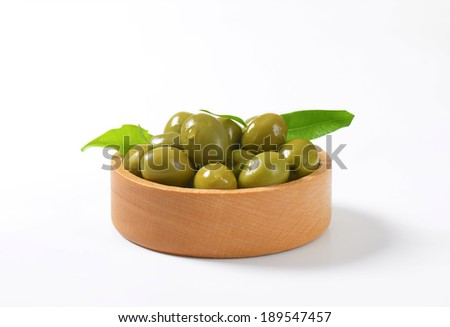 side view of wooden bowl with green olives - stock photo