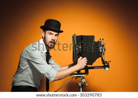 side view of young  afraid man in hat as photographer with retro camera on an orange background - stock photo