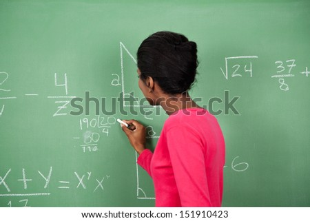 Side view of young African American female teacher solving mathematics on board in classroom - stock photo