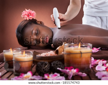 Side view of young African American woman undergoing microdermabrasion therapy at beauty spa - stock photo