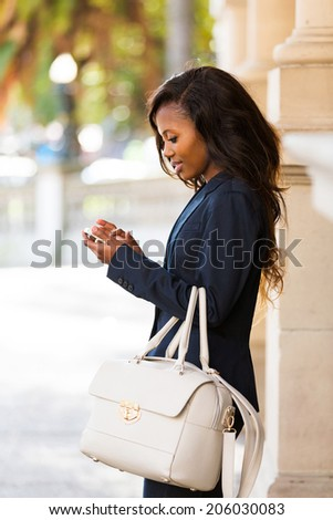 side view of young african woman using smart phone - stock photo