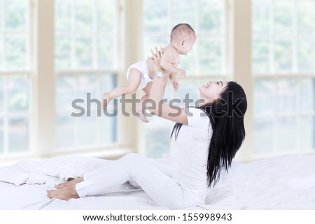 Side view of young asian mom lifting happy baby into air above head - stock photo