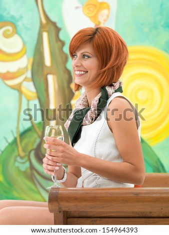 side view of young attractive redhead woman sitting and holding a glass of wine in her hand, looking in front of her and smiling, with colorful painting on background - stock photo