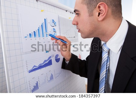 Side view of young businessman analyzing graph with pen in office - stock photo