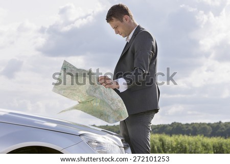 Side view of young businessman reading map by car at countryside - stock photo