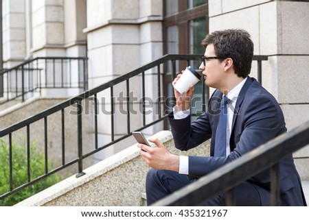 Side view of young businessman sitting on stairs of beautiful building, drinking coffee and using phone - stock photo
