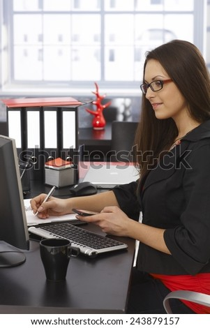 Side view of young businesswoman sitting at desk, working on computer, holding mobilephone. - stock photo