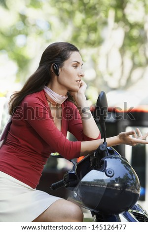 Side view of young businesswoman using wireless headset while sitting on scooter - stock photo