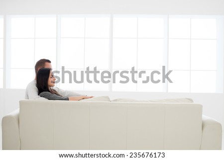 side view of young caucasian couple relaxing together on couch looking in front - stock photo