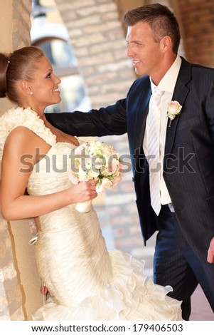 Side view of young couple on wedding-day, smiling happy outdoors, bride leaning against wall. - stock photo