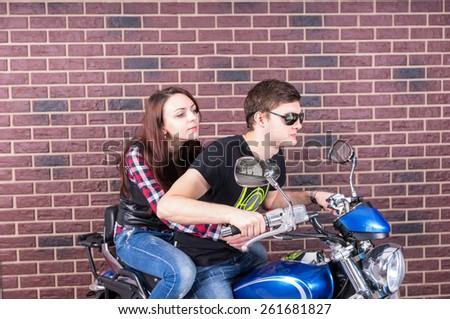 Side View of Young Couple Riding Two Up on Classic Blue Motorcycle in front of Brick Wall - stock photo