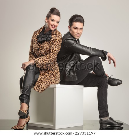 Side view of young fashion couple sitting on a white cube holding their legs crossed. - stock photo