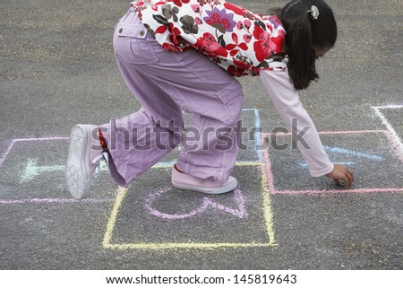 Side view of young girl playing hop-scotch in playground - stock photo