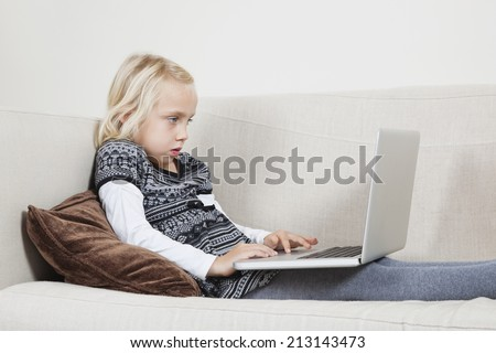 Side view of young girl using laptop on sofa - stock photo