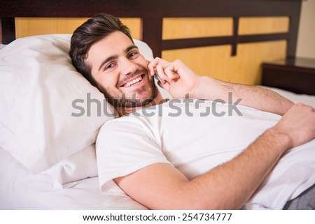 Side view of young handsome man is lying on bed, speaking by phone and looking at the camera. - stock photo