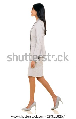 side view of young indian businesswoman walking on white background - stock photo