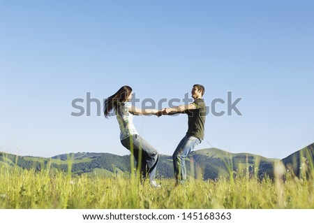 Side view of young loving couple playing against mountain range and clear sky at park - stock photo